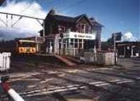 Class 303 about to cross over the level crossing at Balloch Central.<br><br>[Ewan Crawford&nbsp;//]