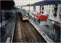 View looking west at Woodhall station. Class 303 entering station.<br><br>[Ewan Crawford&nbsp;//]