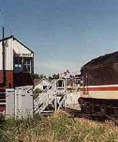 Looking west at Elgin west signalbox and level crossing. Class 47 and passenger train and token hoops exchange.<br><br>[Ewan Crawford&nbsp;//]