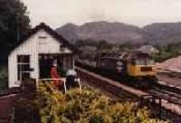 Class 47 hauled passenger train running south through Dunkeld station. View looking north from the former locomotive shed showing the signalbox.<br><br>[Ewan Crawford&nbsp;//]