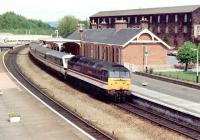 A class 47 drags a dead electric train south through Dumfries in June 1991. The now demolished ex-Caledonian goods depot dominates the background on the east side of the station.<br><br>[John Furnevel&nbsp;23/06/1991]
