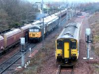 A busy scene at the north end of Millerhill yard on 10 December 2002. On the left a coal train is passing through behind a class 66, in the centre <I>Loadhaul</I> liveried 56118 is leaving for the north with a freight, while on the right 150250 is running into the turnback siding after recently terminating at Newcraighall on a service from Bathgate. The DMU will shortly form the next service to Dunblane.<br><br>[John Furnevel&nbsp;10/12/2002]