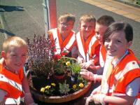 Crosshouse Primary School pupils Liam Orton, Kai Gallagher, Cameron Sinclair, Jack Ralston, and Emma MacDonald tending to one of their planters at Hairmyres station. [See adjacent news item]<br> <br><br>[ScotRail&nbsp;30/08/2012]