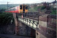 Westbound train leaves Old Kilpatrick over  roadbridge to its west.<br><br>[Ewan Crawford&nbsp;//]