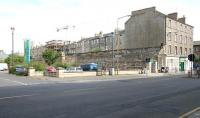 The Great Wall of Leith. The north wall of Leith Central station in 2006, now forming the boundary of the Co-op Supermarket car park. View northwest across Easter Road, with part of the western abutment of the railway bridge that once spanned the road still standing. The grey roof of the Co-op supermarket is visible on the extreme left of the picture, while just out of shot alongside is 'Leith Waterworld', a leisure facility which was also built on the site of the old station. [See image 11664]  <br><br>[John Furnevel&nbsp;22/07/2006]