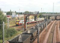 Shortly after a stop at Rutherglen station in August 2006 a Dalmuir - Lanark train heads towards Rutherglen Central Junction, passing the tail end of a train of westbound coal empties bound for Hunterston.<br><br>[John Furnevel&nbsp;15/08/2006]