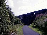 Looking South East, loaded coal hoppers from Hunterston trundle over the bridge at Elderslie Fly Under behind an EWS Class 66 going in the direction of Glasgow<br><br>[Graham Morgan&nbsp;16/08/2006]