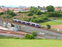 A Glasgow Queen Street - Dunblane service runs past the washing plant at the north end of the new ScotRail depot at Eastfield on 27 August 2006. Note the fenced off embankment beyond the train, from which an 8-span plate girder viaduct once carried the Caledonian freight line actoss the E&G. [See image 9082]<br><br>[John Furnevel&nbsp;27/08/2006]