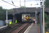 Photograph taken looking north west from the footbridge at Whifflet station in August 2006. A train for Glasgow Central has just left the platform and passed under the bridge carrying Whifflet Street (A725). The train is turning west at Whifflet North Junction heading for its next stop at Kirkwood.<br><br>[John Furnevel&nbsp;24/08/2006]