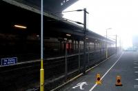 Platforms 20 & 21 stand in the early morning fog under the North Bridge with only a Coke machine and the coned-off markings of a previous nights murder victim for company. Sept 2006. <br><br>[John Furnevel&nbsp;/09/2006]