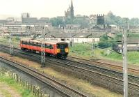 Train from Ayr to Glasgow passing Paisley Abbey in middle background.<br><br>[Brian Forbes&nbsp;//1992]