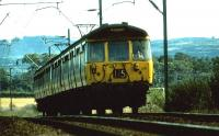 A Helensburgh bound pair of 303s pass the site of the Ardmore yard in August 1975.<br><br>[John McIntyre&nbsp;/08/1975]