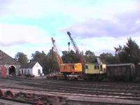 Two multi use cranes. Diesel and steam at Aviemore shed 60B.<BR/>The red car is acting as a scotch, maybe.<br><br>[Brian Forbes&nbsp;23/09/2006]