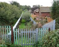 Looking south from the B721 road over the former station at Annan Shawhill on 12 October 2006 along the route that ran to the Solway Viaduct. The pipeline now occupying the trackbed carries waste (?) water from Chapelcross nuclear power station to the Solway Firth. [See image 19418]<br><br>[John Furnevel&nbsp;12/10/2006]