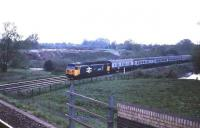 An eastbound express on the west of England main line in 1985 behind 50037 <i>Illustrious</i> about to pass under the Salisbury line.  <br><br>[John McIntyre&nbsp;//1985]