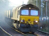A very smoky 66143 passing through Johnstone with loaded coal hoppers.<br><br>[Graham Morgan&nbsp;24/01/2007]