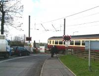 A westbound train for Glasgow Central leaving Kirknewton station on 5 March 2007 via the infamous half-barrier level crossing over the B7031. <br><br>[John Furnevel&nbsp;5/03/2007]