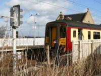 The driver of a stopping train activates the half-barrier level crossing west of the station prior to leaving Kirknewton for Glasgow Central on 5 March 2007.<br><br>[John Furnevel&nbsp;5/03/2007]
