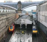 Virgin and GNER services wait in the pouring rain at the Waverley sub platforms on 9 March 2007. The recently modified walkway can be seen above the platform canopy, while through the arch of North Bridge is part of the new Edinburgh Council HQ.  <br><br>[John Furnevel&nbsp;09/03/2007]