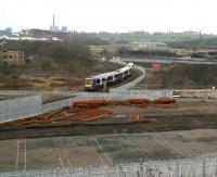 A Queen Street train off the Cumbernauld line heads along the south side of the Cowlairs triangle on 26 March 2007. It has just cleared the level crossing controlling access to the works site for the new MDU and signalling centre.   <br><br>[John Furnevel&nbsp;26/03/2007]