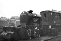 Tales of old Ferryhill 3. The wagon mounted tank looks like the waste oil container. Several oil drums and barrows for transporting them around the shed can also be seen. The converted Gresley teak bodied coach forms part of the Ferryhill breakdown train, C. 1973.<br><br>[John McIntyre&nbsp;/01/1973]