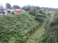 View south from the bridge over the trackbed at Tynehead in August 2002 showing the steep climb away from the platforms immediately below the bridge. The former station building and goods yard are on the left with the trackbed of the spur running north off the main line to reach the yard visible in the background. <br> <br><br>[John Furnevel&nbsp;12/08/2002]