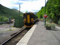 Glasgow Queen Street train leaving Arrochar and Tarbet on 28 May passing the timber loading area on the left.<br><br>[John McIntyre&nbsp;28/05/2007]