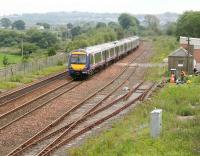 A westbound Edinburgh - Glasgow shuttle passing the site of Manuel station in July 2007. Originally opened as Bo'ness Junction in 1842, the station was eventually closed in March 1967. The line to Boness, now owned and operated by the SRPS, can be seen on the left beyond the wire fence.<br><br>[John Furnevel&nbsp;07/07/2007]