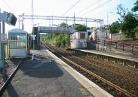 View across the platforms at Woodhall station early on a Sunday morning in July 2007. Outside the station entrance on Glasgow Road a solitary passenger can be seen utilising the interchange facilities (formerly <I>waiting for a bus</I>).<br><br>[John Furnevel&nbsp;29/07/2007]