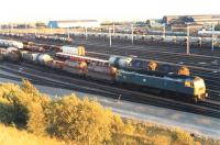 A class 47 at the head of a rake in Mossend yard during a sunny evening in 1989. The Chivas tanks (first two vehicles) are probably destined for Keith.<br><br>[Ewan Crawford&nbsp;//1989]