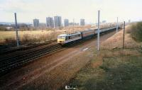 A brand new Class 90 passes Shieldmuir heading south. On a test run the locomotive and rake had come up the WCML, passed round the junctions at Mossend and was now heading south. This is now the site of Shieldmuir station.<br><br>[Ewan Crawford&nbsp;//1989]