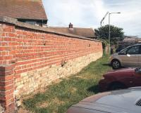 All that remains of Seahouses station on the North Sunderland Light Railway in the summer of 2007 - the lower (lighter brick) section of the wall alongside the village car park once formed part of the platform face. [See image 41104]<br><br>[John Furnevel&nbsp;18/08/2007]