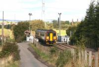 A Motherwell - Cumbernauld service runs over Heatherbell level crossing on 25 September 2007 on its way from Gartsherrie South to Garnqueen North Junction. In the right background stand chimneys of the former Gartliston fireclay works, whose products once lined many a blast furnace in the Coatbridge area and beyond.<br><br>[John Furnevel&nbsp;25/09/2007]