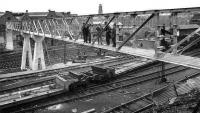 Mystery picture...thanks to all who responded to the request to help identify the old photograph - in particular to Bill Roberton who finally nailed it. The picture was in fact taken looking north across the lines outside Princes Street station, Edinburgh in 1963. Amongst the features still standing are the tenements in the right background which form the rear of Rutland Square and the tower on the skyline, which is part of St Georges West church on Shandwick Place. I have emailed details to Alex Dyne who is paying a visit to Edinburgh next week and who had requested help in identifying the location - an old family photograph of his late father who not only appears in the picture but was also the engineer who designed the bridge on behalf of the SSEB - Ed. (Old family photograph).<br><br>[Alex Dyne Collection&nbsp;28/04/1963]
