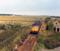 A class 26 powers up the gradient past the abandoned station at Rathen with the daily goods from Fraserburgh to Aberdeen, in August 1978.<br><br>[John Williamson&nbsp;14/08/1978]