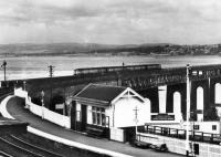 Taken from a b&w postcard. A four car 101 sets out over the Tay Bridge northwards towards Dundee. The Wormit up platform is in pristine condition. Date mmm...late 1950s at a guess.<br><br>[Brian Forbes Collection&nbsp;//]
