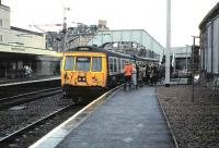 Passengers boarding a Dalmuir service formed by 303 027 at Hamilton Central in March 1985.<br><br>[David Panton&nbsp;/03/1985]