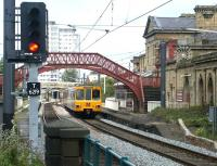 A Tyne & Wear Metro service, passes the closed station at Monkwearmouth in July 2004 on the northern approach to Sunderland. The 1848 station, originally built by the YN&B as a terminus, lost much of its importance in 1879 when the line crossed the River Wear to reach the centre of Sunderland. It closed in 1967 and is now an acclaimed museum. <br><br>[John Furnevel&nbsp;10/07/2004]