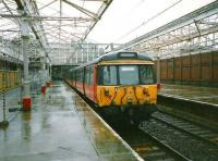 Platform 1 at Helensburgh Central in July 1997 with the canopy glazing removed and a miserable looking 303 001 standing in the rain.<br><br>[David Panton&nbsp;/07/1997]