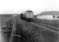 A class 24 with a very light load on the Saturday goods from Fraserburgh to Aberdeen Craiginches, passes the 18th green at Fraserburgh Golf Club in the summer of 1971. Almost all of this view has now disappeared. The St Combs road over-bridge was demolished more than 15 years ago, and the golf club-house itself has been re-built after a recent fire.<br><br>[John Williamson&nbsp;//1971]