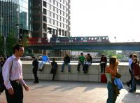 A city bound train on the Docklands Light Railway emerges from the office blocks surrounding Heron Quays station in July 2005, running out onto the bridge over the old East India Dock as it heads for Canary Wharf.<br><br>[John Furnevel&nbsp;22/07/2005]