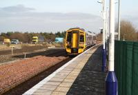 An Edinburgh - Bathgate service pulls into the platform at Uphall on 15 February 2008 as traffic continues west along the M8. Note the area now pegged around the site of the second platform as well as the work underway beyond in preparation for new infrastructure on the north side of the station.<br><br>[John Furnevel&nbsp;15/02/2008]