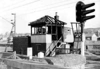 The signalbox at Cardross was set alight very late in the day of 26 April 1971 by a drunk passenger who had just arrived on a Helensburgh bound train. The remains of the box are seen early in the morning of 28 April 1971. The signalman at the time of the incident was a friend, Jack Vickers. A temporary control centre was set up in an old waiting room on the up platform and an interlocked single lever ground frame was installed in front of the former box to release the level crossing gates. The arrangement lasted until the North Clyde resignalling was completed following which the area was controlled from Yoker.<br><br>[John McIntyre&nbsp;28/04/1971]