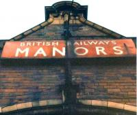 British Railways enamel name board in NER tangerine below the clock tower at the old Manors North station, Newcastle, on 14 February 1982. [See image 13227]<br><br>[Colin Alexander&nbsp;14/02/1982]