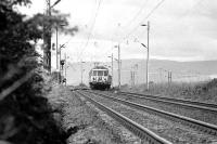 With the Argyll hills in the background a pair of Class 303 units approaches Geilston level crossing, west of Cardross, with an eastbound service in 1974.<br><br>[John McIntyre&nbsp;/03/1974]