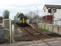 156473 waits for the crossing barriers to close before leaving Moss Side for Kirkham on a Blackpool South to Colne service. Although substantially modified the house in the picture is the original station house.  <br><br>[Mark Bartlett&nbsp;26/04/2008]