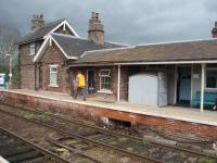The signaller walks down Hammerton platform to operate the crossing gates. The small grey wooden building houses the lever frame for the points and semaphore signals and the rodding and wires can be seen below. The block instruments are in the office behind and the single line token pouches are just inside the doorway.<br><br>[Mark Bartlett&nbsp;28/04/2008]