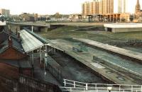 The north side of Manors station in 1982, showing the remains of through platforms 1 & 2 and bays 3-5. In the foreground is part of the long wooden footbridge that provided a link to the stations east platforms at that time. The new <I>blockhouse</I> building in the right background is the Tyne & Wear Metro and beyond that are the remains of New Bridge Street goods depot (originally Picton Street), former terminus of the Blyth & Tyne Railway, replaced in 1909 by Manors (North) on the extension to the junction with the ECML.<br><br>[Colin Alexander&nbsp;//1982]