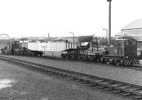 Scene at Rosyth Dockyard in the 1980s. Two Planet 0-4-0 diesel mechanical locomotives sandwich a curious-looking beam (?) wagon built by Head Wrightson, with a pair of 6-wheel bogies at each end. Presumed internal user. [Additional from Keith Falconer - this could be a nuclear submarine hot core carrier - the fuel rods for a sub would be in a round vessel which fitted a recess in the centre of the wagon. If on the main line it would normally be escorted by an armed guard in a converted mk1 coach.]<br><br>[Bill Roberton&nbsp;//]