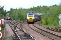 A silver power car on a white stripe HST 125 set heads south at Ladybank on 18 May 2008, passing an EWS class 66 waiting for the road on the Perth line with a ballast train.<br><br>[Brian Forbes&nbsp;18/05/2008]